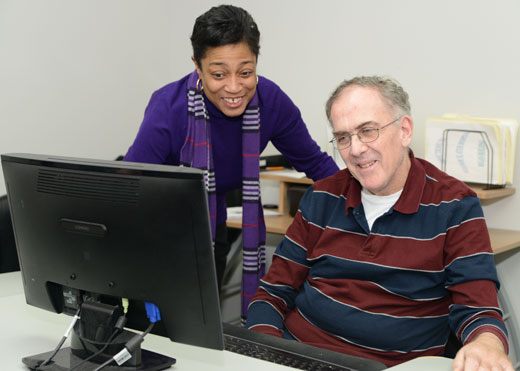 Staff person assisting gentleman at the computer